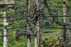 Electricity pole cables bonded in a intersection. Electricity cables in phuket, thailand. close up on the electricity pillar and cable intersections Royalty Free Stock Images