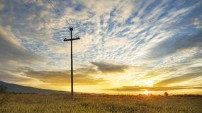 Electricity pole and harvest field on colorful sky Stock Images