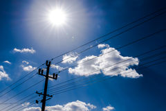 Electricity pole with sun in background. Electricity pole and wires, with sky and clouds in backgrounc, solar power electricity concept Royalty Free Stock Images