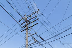 Electricity pole with wires grid with blue sky Royalty Free Stock Image