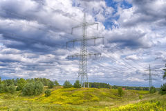 Electricity poles, landscape with blue sky and yel. Hdr, landscape with electricity poles on the hill with yellow flowers and blue cloudy sky stock images
