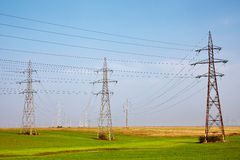 Electricity poles on a meadow Royalty Free Stock Photography