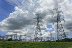 Electricity poles and wires against dramatic blue cloudy sky Royalty Free Stock Photos