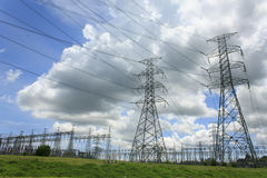 Electricity poles and wires against dramatic blue cloudy sky Royalty Free Stock Photography