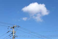 Electricity post against a blue sky with clouds. Electricity pylon or post against a clear blue sky with white clouds Royalty Free Stock Photos