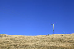 Electricity post in dry grass field Royalty Free Stock Photo