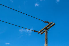 Electricity post in sky. Electricity pole with cables on rich blue sky Stock Photography