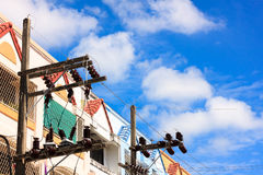 The electricity post and townhouses blue sky background.In the Stock Photos