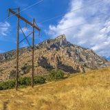 Electricity posts on grass beside a rocky mountain royalty free stock image