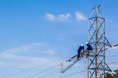 Electricity Power Cable Repairs Electricians. Electrical Power Cable Repairs by Electricians on steel tower stock photo