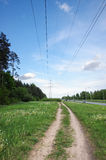 Electricity power lines above path in the meadow Stock Photo