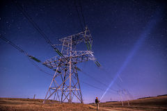 Electricity power poles on alone man -  night sky and stars Royalty Free Stock Photo
