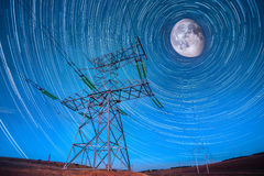 Electricity power poles on night sky and startails moon backgrou Stock Photos