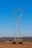 Electricity Power Pylons against Bright Blue Sky Stock Photo