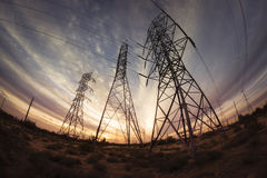 Electricity power pylons at sunset. Wide angle perspective of electricity power pylons at sunset Royalty Free Stock Photo