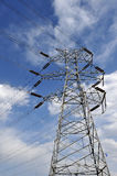 Electricity pylon. Power tower standing in the blue sky and white clouds Royalty Free Stock Images