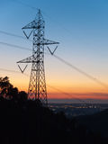 Electricity pylon. At sunset with lights in the background royalty free stock photo