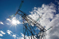Electricity pylon. Electricity power distribution pylon with sun and clouds Stock Photos
