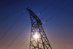 Electricity pylon. Sun setting behind a  electricity pylon Royalty Free Stock Photos