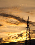 Electricity pylon. Silhouetted against beautiful cloudy and stormy sky at sunset Royalty Free Stock Images