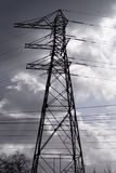 Electricity pylon. Silhouetted against stormy sky stock images