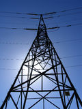 Electricity pylon. Interesting, dizzying angle of an electricity pylon towering over the ground, with the sun helping to silhouette the shape royalty free stock photos