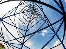 Electricity pylon abstract on blue cloudy sky. Beautiful bottom view. Beautiful distortion of straight lines as you move away from the viewer Stock Images