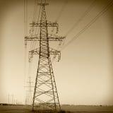 Electricity pylon against blue cloudy sky. Vintage Stock Photos