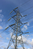 Electricity pylon against blue sky on a sunny day Royalty Free Stock Image