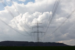 Electricity pylon against sky and forest Royalty Free Stock Photo