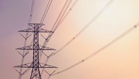 Electricity pylon against the violet and orange background. Electricity pylon against the violet and orange color background stock photo