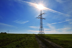 Electricity pylon aligned with the sun. Image with a big electricity pole with cables in all directions pointing to the bright sun on the blue sky. Two different Royalty Free Stock Photography