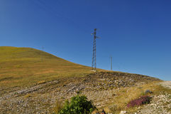 Electricity pylon and blue sky on the Apennines mountains Royalty Free Stock Photography