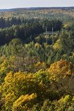 Electricity pylon in colorful forest in autumn Royalty Free Stock Image