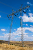 Electricity pylon. Through countryside fields under blue cloudy sky stock photo