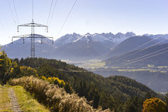 Electricity pylon crossing the alps in the Tirol. Austria above forested slopes with alpine peaks in the background in a scenic landscape Stock Photography