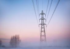 Electricity pylon in fog stock image