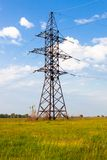 Electricity pylon on the green grass against the cloudy sky Royalty Free Stock Image