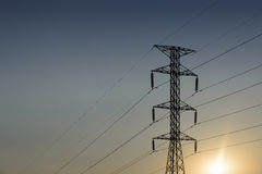 The electricity pylon and the hi-voltage cable with  the silhoue Royalty Free Stock Photo