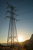 Electricity pylon. Large electricity pylon in a hilly landscape at sunrise Royalty Free Stock Images