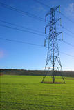 Electricity pylon in meadow. British electricity pylon carrying national grid high voltage power cables, middle of a farmers field Stock Photo