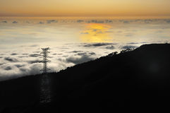 Electricity pylon over valley at sunset, Lomba das Stock Images
