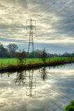Electricity pylon reflected in water Stock Photography