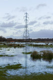 Electricity Pylon with reflection. High voltage Pylon with its reflection in flooded Christchurch Meadows, Dorset, England, United Kingdom Royalty Free Stock Image