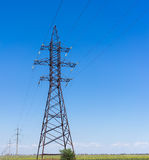 Electricity pylon silhouette against blue sky background. High voltage tower Stock Photography
