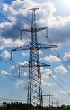 Electricity pylon silhouetted against blue sky background. High voltage tower royalty free stock image