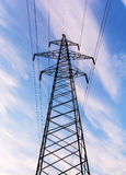 Electricity pylon silhouetted against blue sky background. High voltage tower Stock Photography