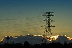 Electricity Pylon Silhouetted At Sunrise. Or sunset Stock Image