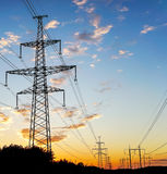 Electricity Pylon - standard overhead power line transmission tower at sunset. Stock Photos