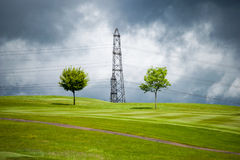 Electricity pylon on a stormy day. Electricity pylon between two trees on a stormy, atmospheric day Royalty Free Stock Photos